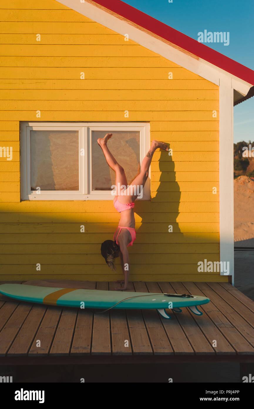 Young woman in pink bikini debout sur les mains contre bâtiment jaune avec voile à proximité au Portugal Photo Stock