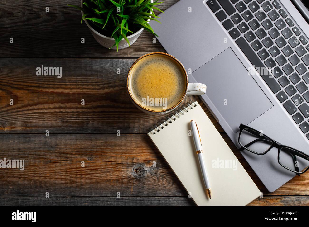 Bureau avec ordinateur portable lunettes bloc notes un stylo et