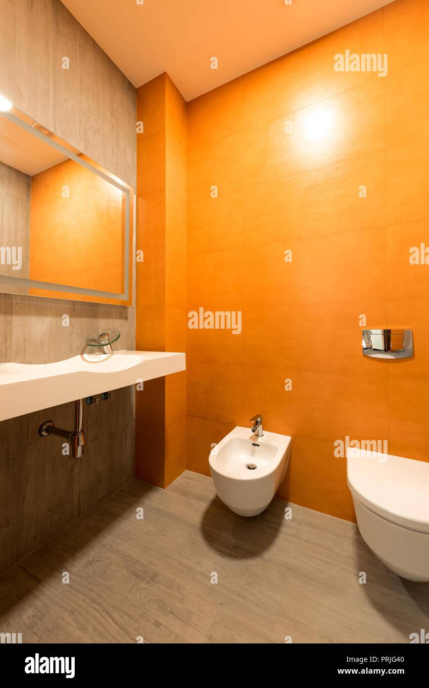 Intérieur de salle de bains moderne en orange et blanc avec ...