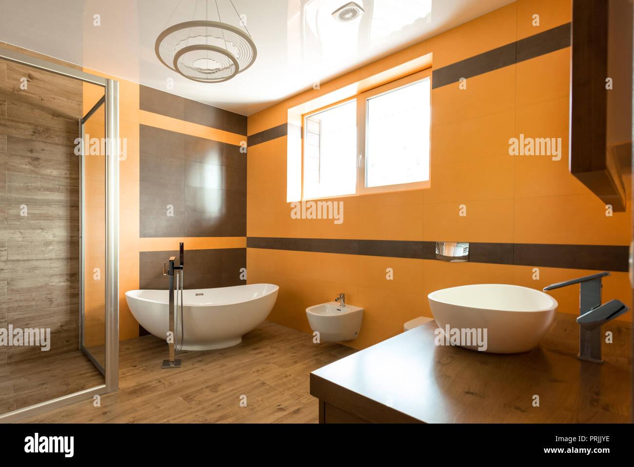 Intérieur de salle de bains en orange et blanc avec baignoire ...
