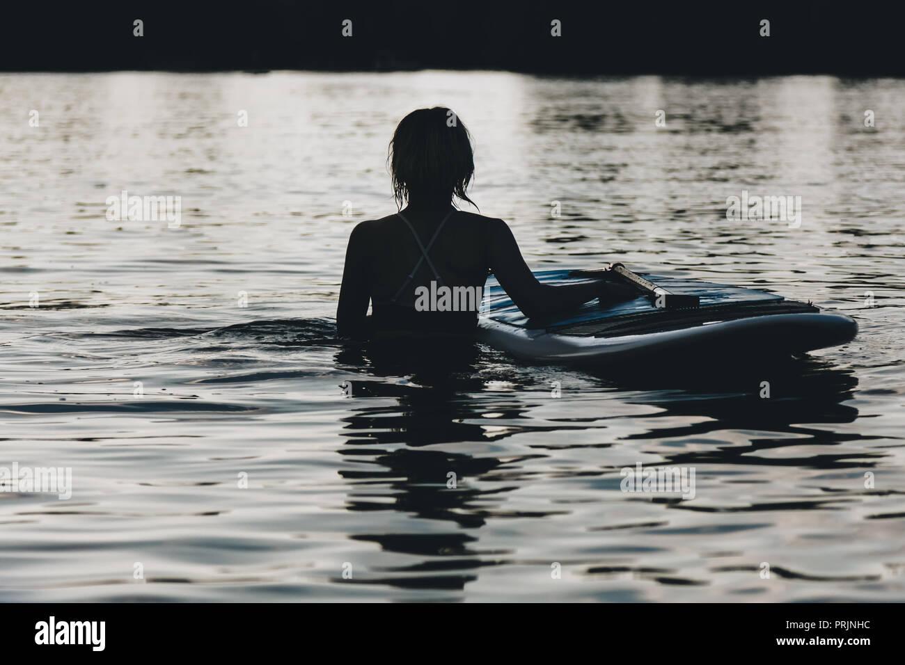 Silhouette de femme dans l'eau avec paddle board Photo Stock