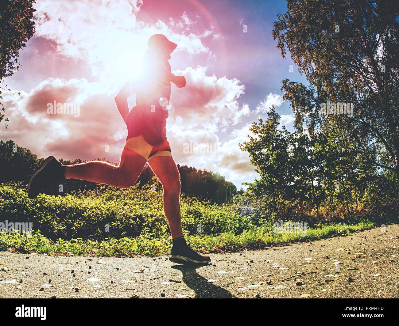 Haut de jogging homme sport dans les arbres d'ombre avec la lumière du soleil derrière lui tout en portant un short noir jaune et bleu tenue de jogging Banque D'Images