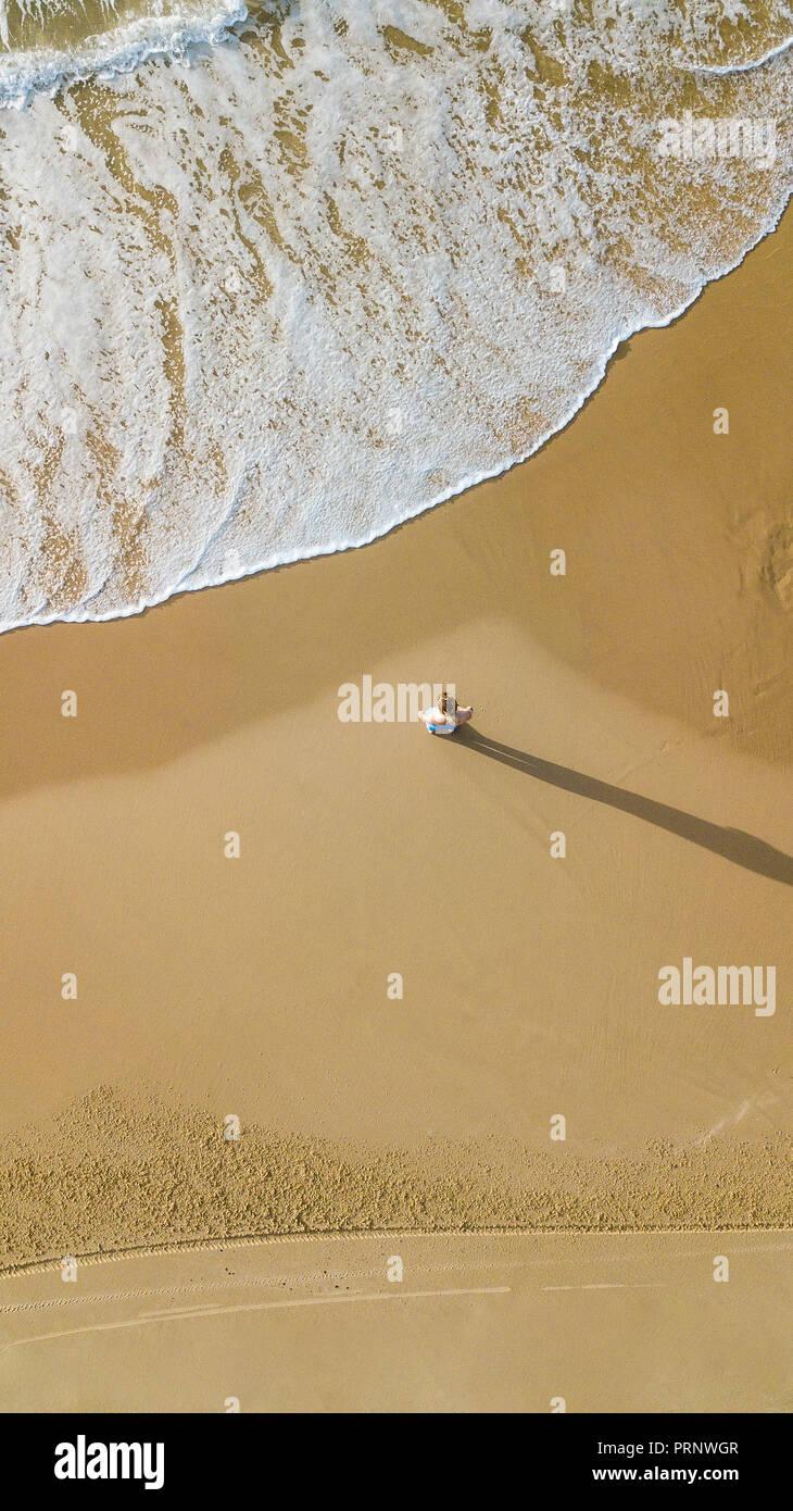 Vue aérienne de la jeune femme debout sur une plage de sable en face de la mer ondulée, Ashdod, Israël Photo Stock