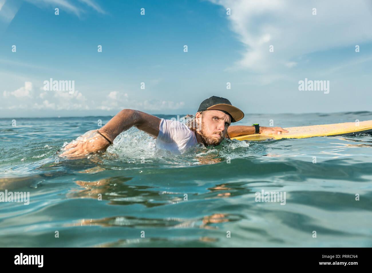 Homme concentré de natation avec surfeur surf board à l'océan sur la plage de Nusa Dua, Bali, Indonésie Photo Stock