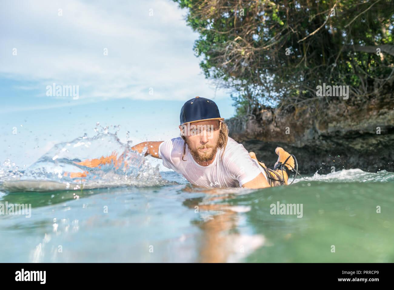 Homme sérieux natation surfer sur le surf de l'océan en bord de plage de Nusa Dua, Bali, Indonésie Photo Stock
