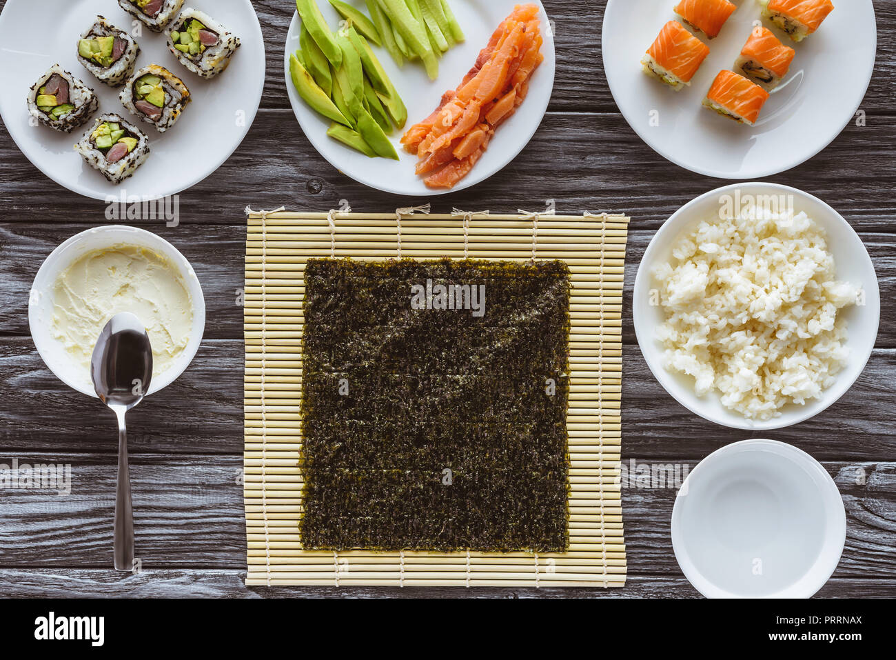Vue de dessus de nori et de délicieux ingrédients pour la cuisson sushi on wooden table Photo Stock