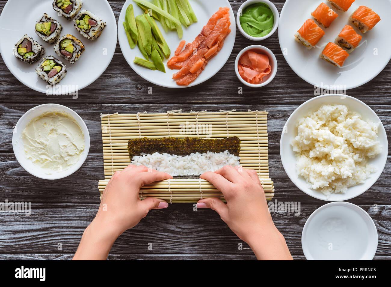 Vue de dessus partielle personne gastronomique cuisine sushi roll Photo Stock