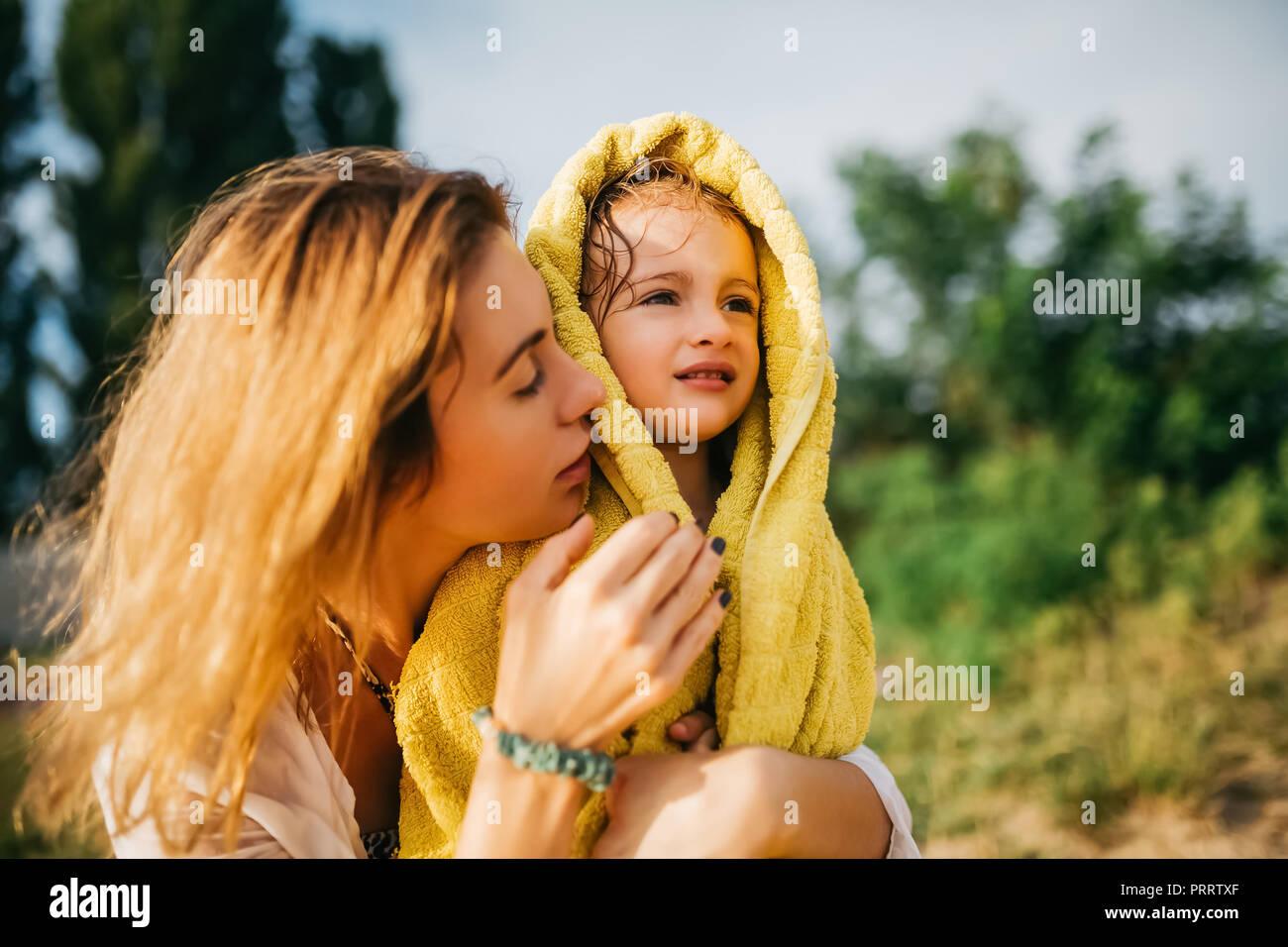 Mère fille couvrant avec une serviette après la baignade dans l'eau Photo Stock