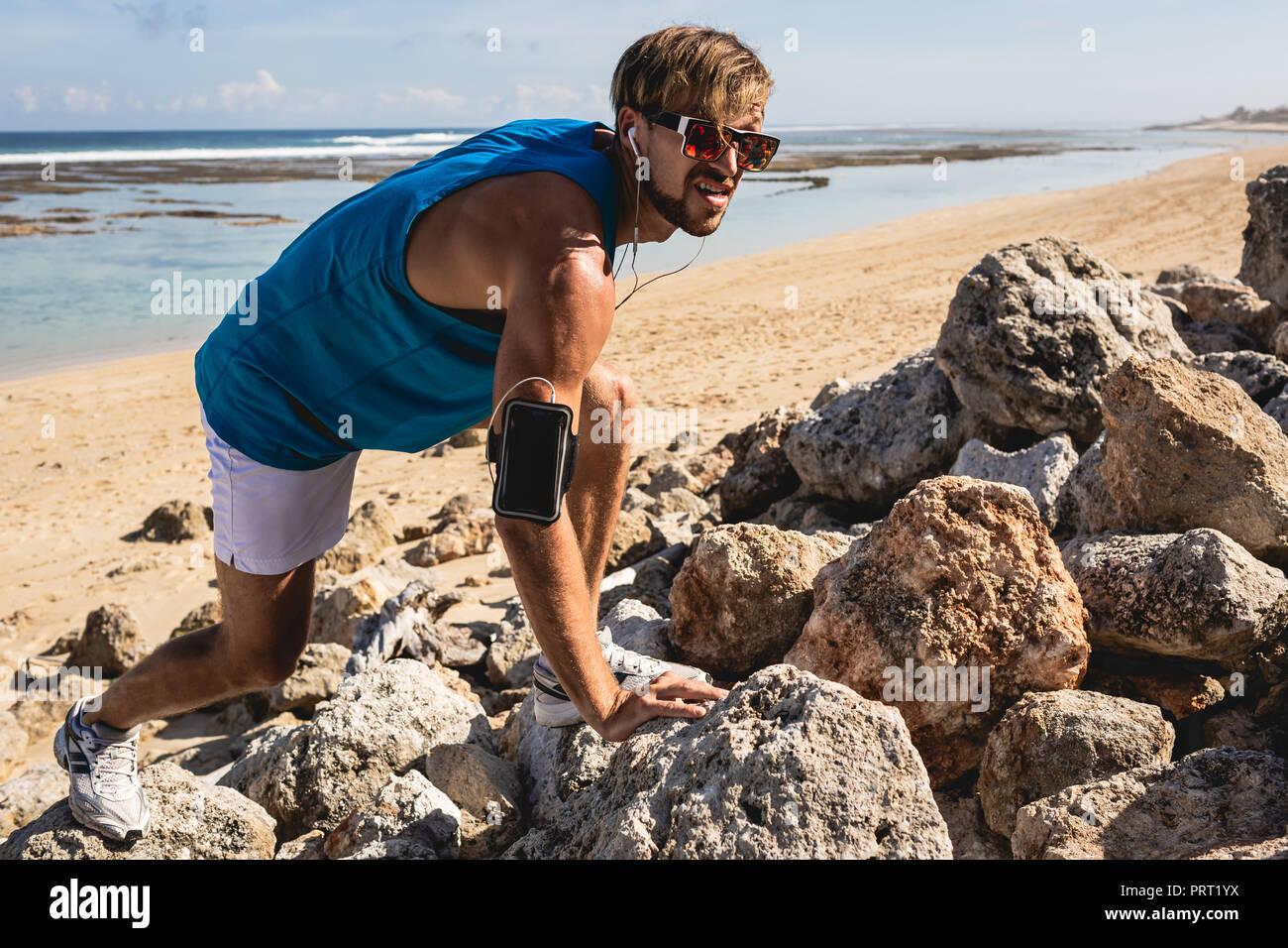 L'homme athlétique de brassard climbing on rocks on beach, Bali, Indonésie Photo Stock