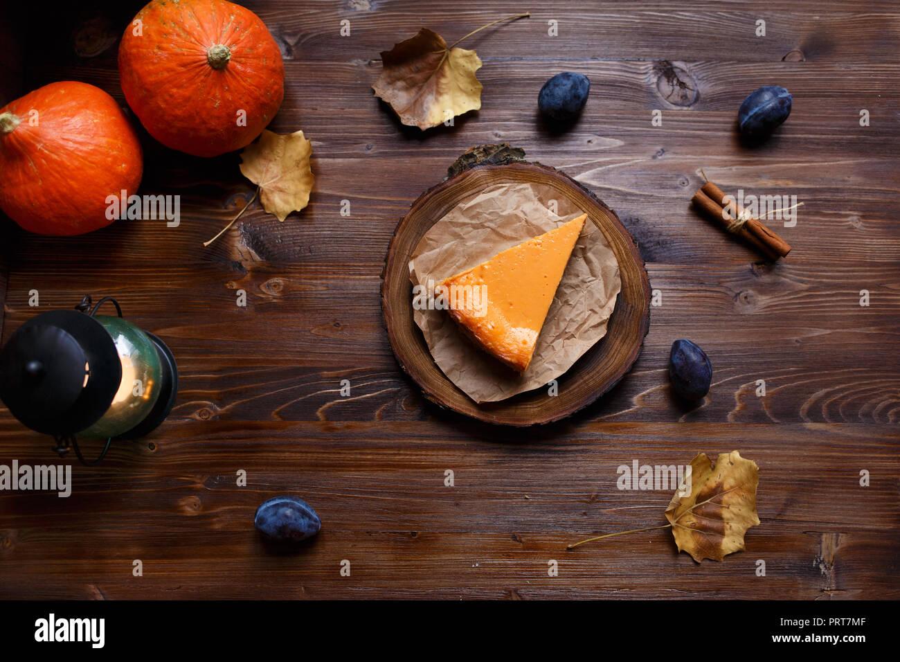 Gâteau au fromage à la citrouille cuite, à la maison, de citrouilles, de prune, de vanille , feuillage sur un tableau noir en bois. L'automne et l'hiver concept confortable. Et Menu restaurant conce Banque D'Images