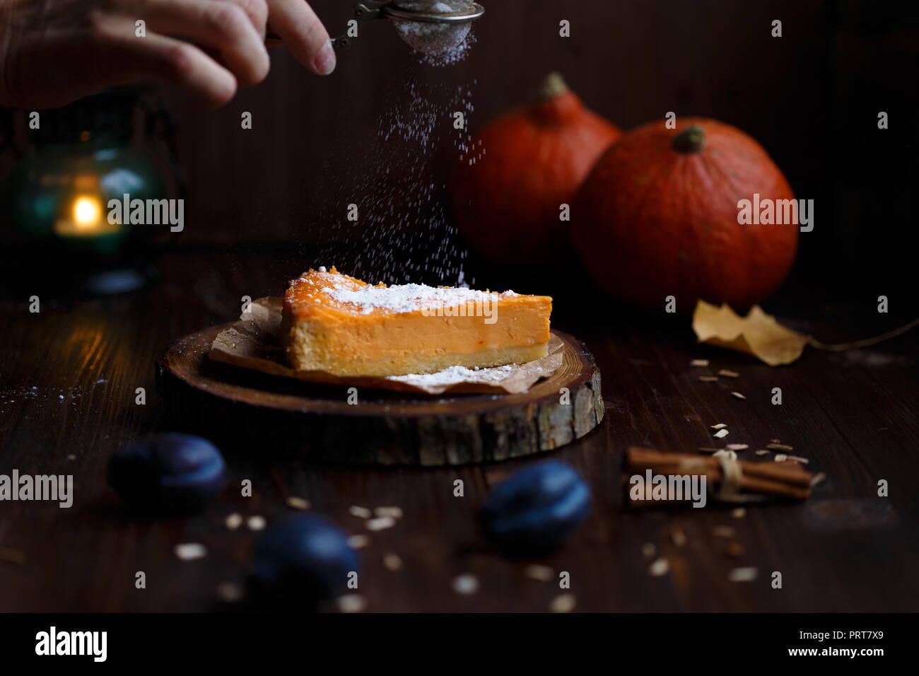 Saupoudre de sucre en poudre à la main féminine sur le gâteau au fromage à la citrouille. Citrouilles, lampe de table, feuillage, la vanille sur un fond sombre en bois. L'automne et l'hiver concept confortable Photo Stock