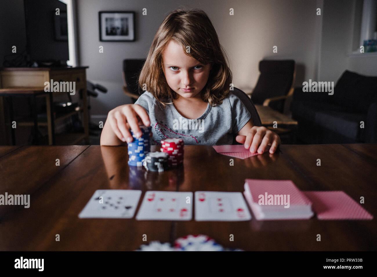 Fille avec pile de jetons de jeu de cartes à jouer à la table, portrait Photo Stock