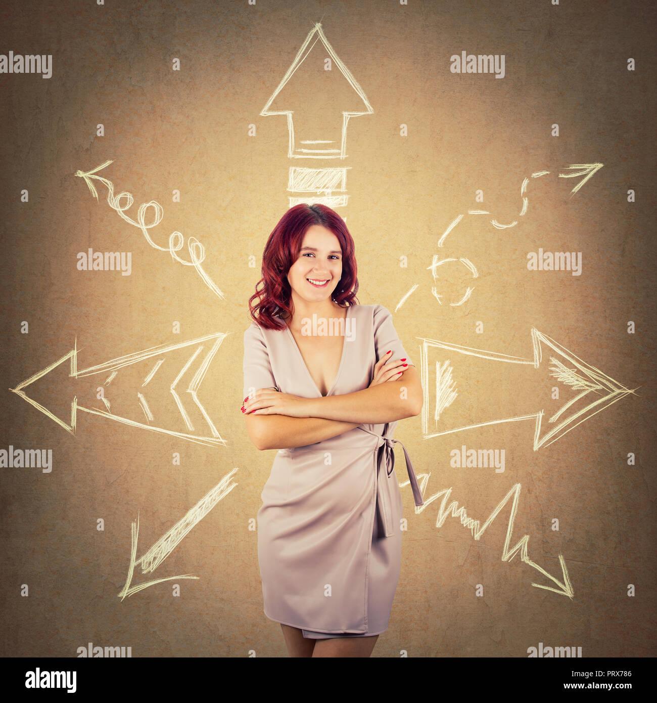 Redhead woman standing with arms crossed et flèches a souligné à différentes directions sur fond coloré. Choix difficile, décider où aller Photo Stock