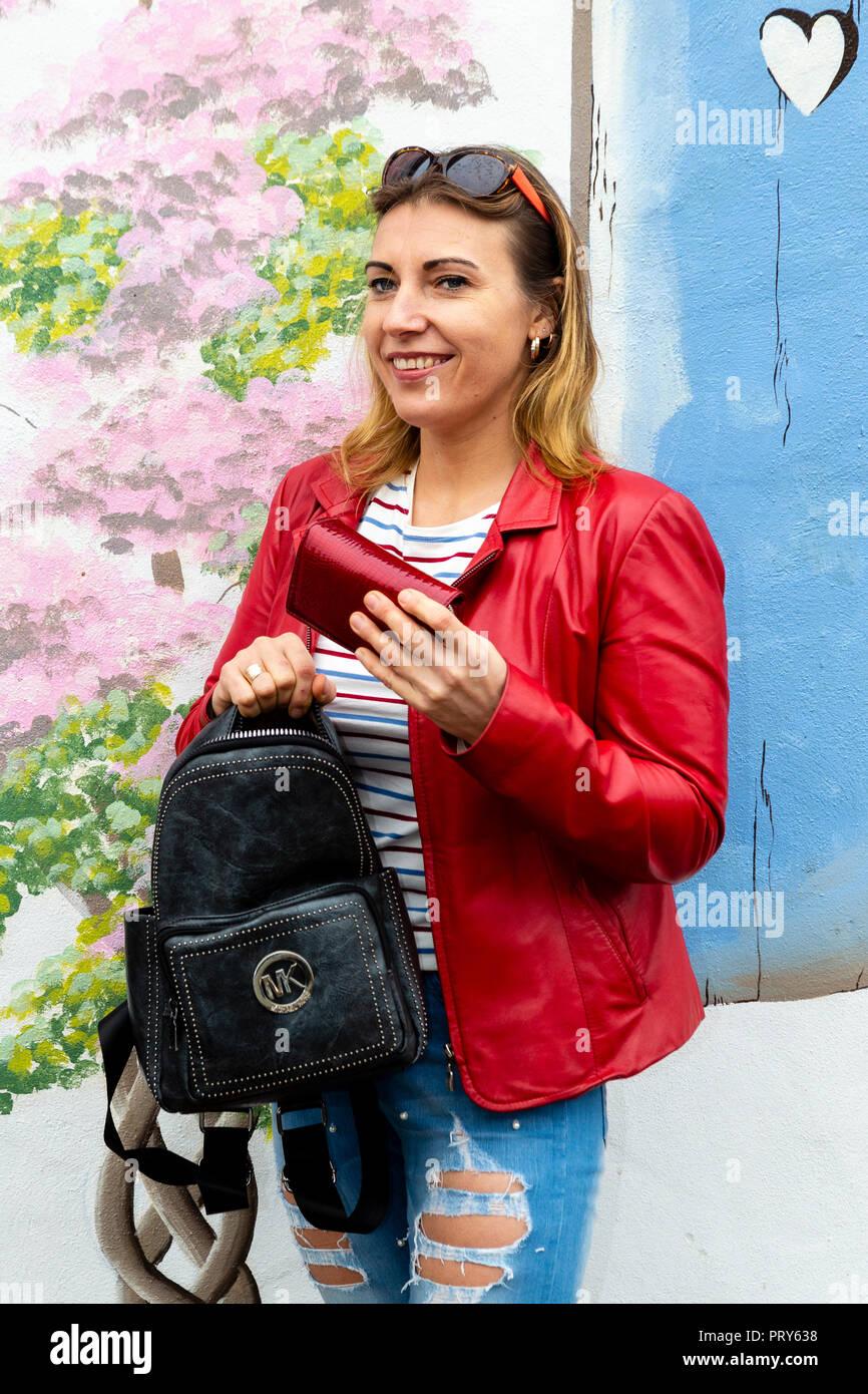 Femme blonde avec sac à main et sac à main, livre de poche, dans la rue Photo Stock