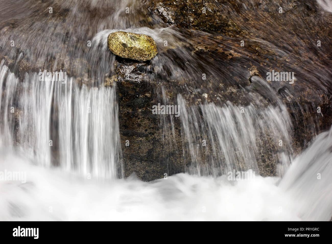 Stone se trouve en face d'une petite chute en courant, ruisseau de montagne, symbolisme, constance, tous contre un Banque D'Images