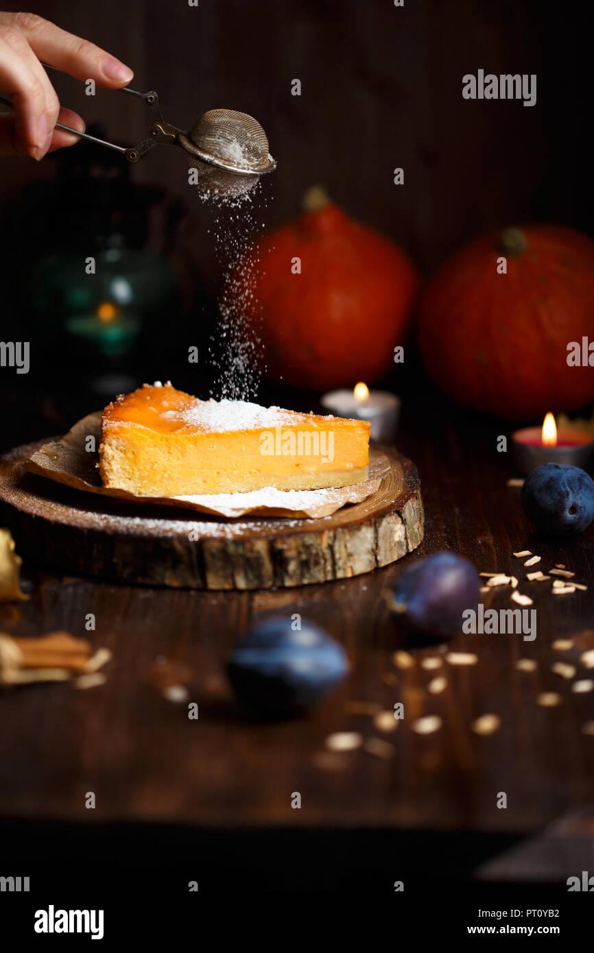 Saupoudre de sucre en poudre à la main féminine sur le gâteau au fromage à la citrouille. Citrouilles, lampe de table, feuillage, la vanille sur un fond sombre en bois. Photo Stock