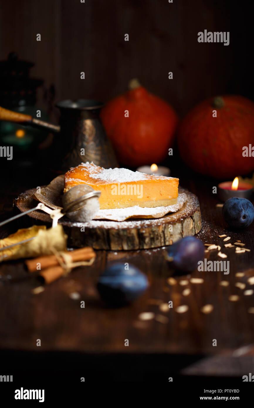 Morceau de gâteau au fromage à la citrouille avec du sucre en poudre, les prunes, les citrouilles, la lampe de table sur un fond de bois foncé Photo Stock