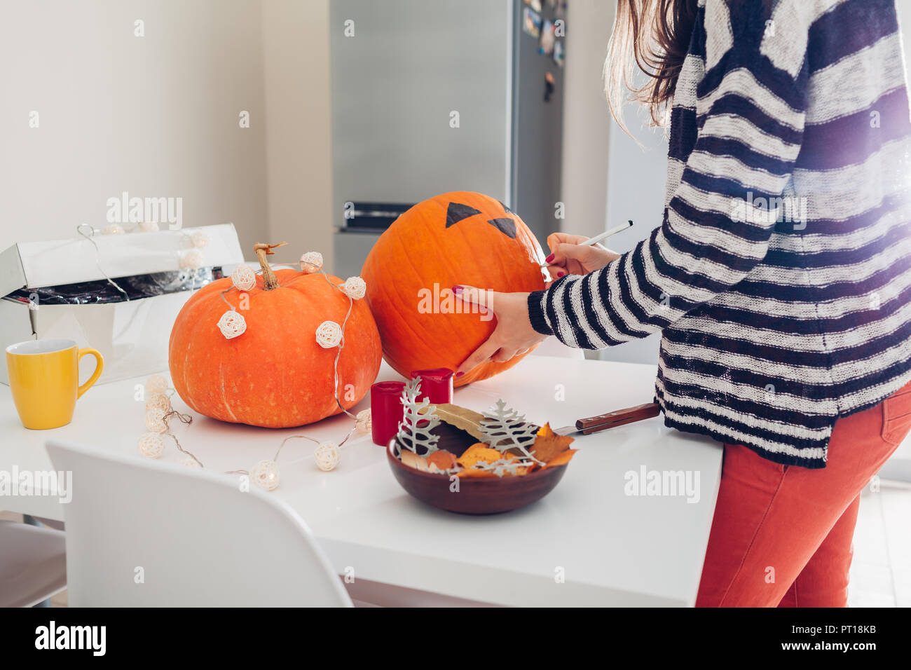 Young woman making jack-o-lanterne pour halloween sur cuisine. Dessiner les yeux, le nez et la bouche avec un crayon sur la citrouille. La préparation de décoration pour maison de vacances Banque D'Images