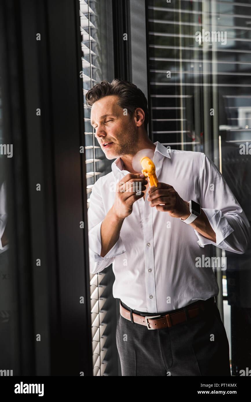 Businessman using hand ventilateur à la fenêtre in office Photo Stock