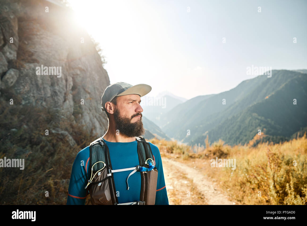 Portrait de l'athlète coureur barbu avec sac à dos dans les montagnes au lever du soleil Photo Stock