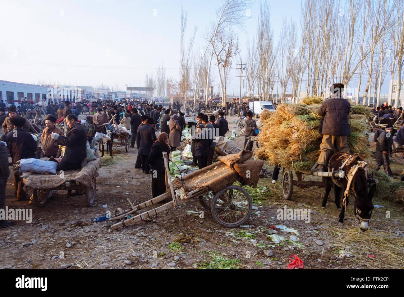 Kashgar, Xinjiang, Chine: Uyghur les gens se rassemblent au mal, le grand bazar du marché du bétail Dimanche de Kashgar. Photo Stock