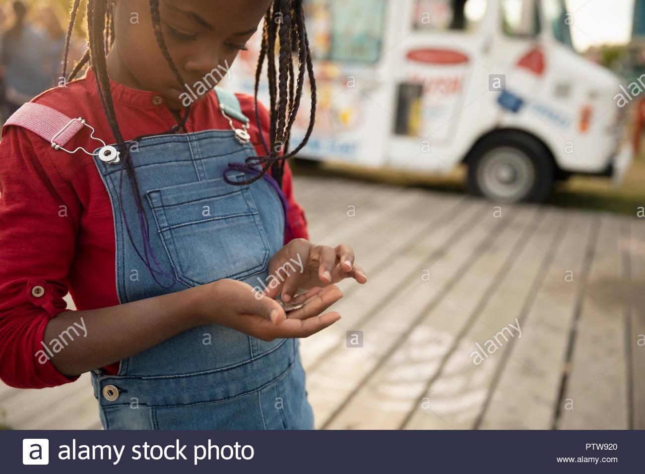Cute girl à compter des pièces à l'extérieur de camion de crème glacée Photo Stock