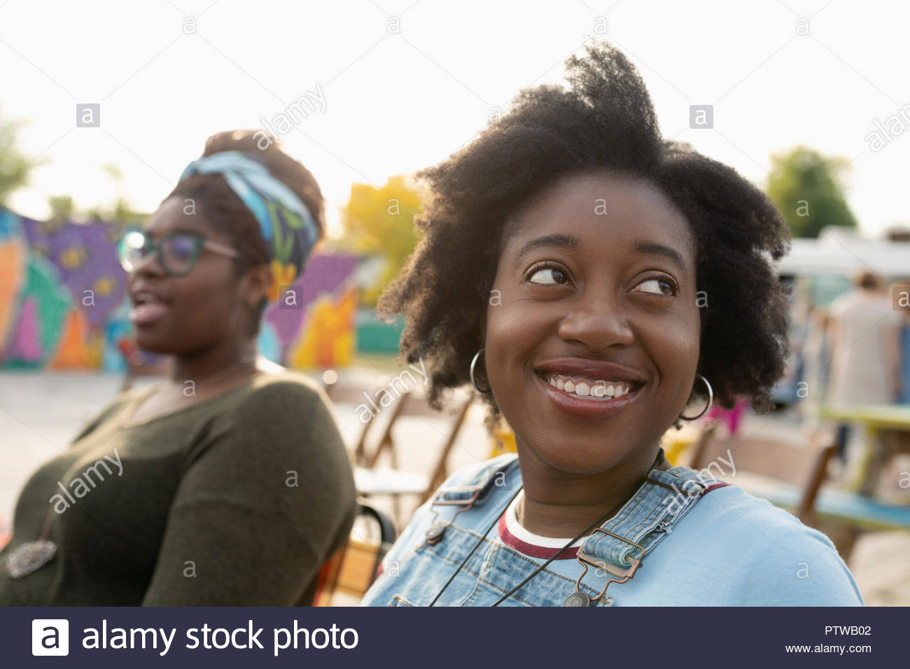 Portrait of smiling young woman looking over shoulder Photo Stock