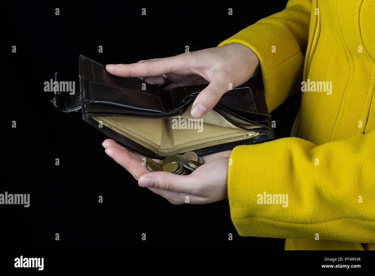 Girl pouring pièces de un sac à main, fond noir, close-up, pièces de monnaie Banque D'Images