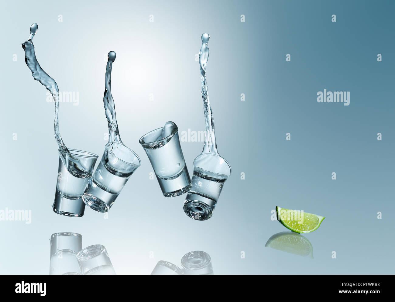 Tequila déversant dans des verres avec lime, studio shot Photo Stock