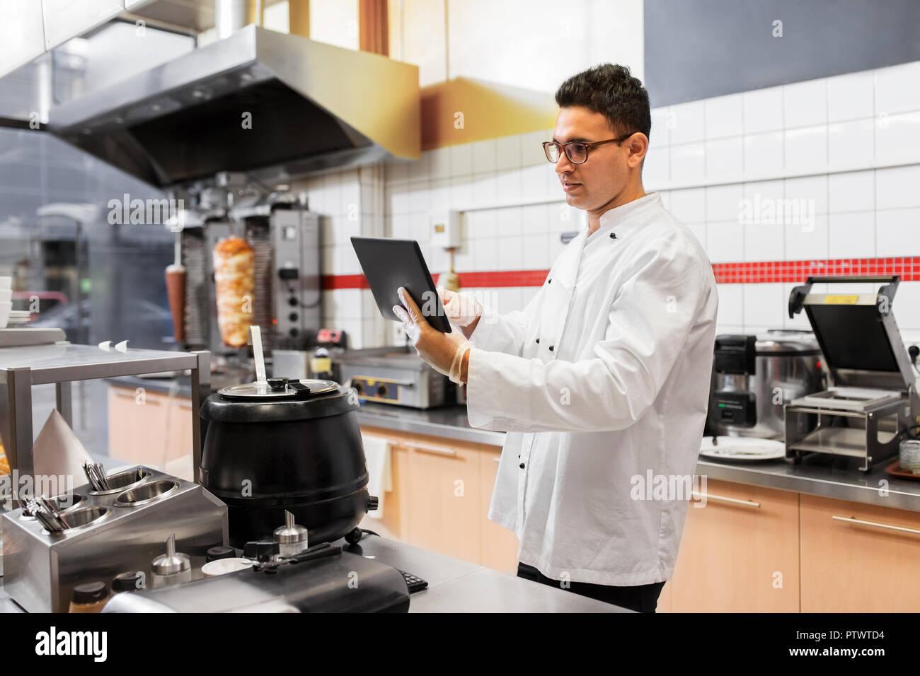 Chef cuisinier avec tablette PC à une cuisine de restaurant Photo Stock