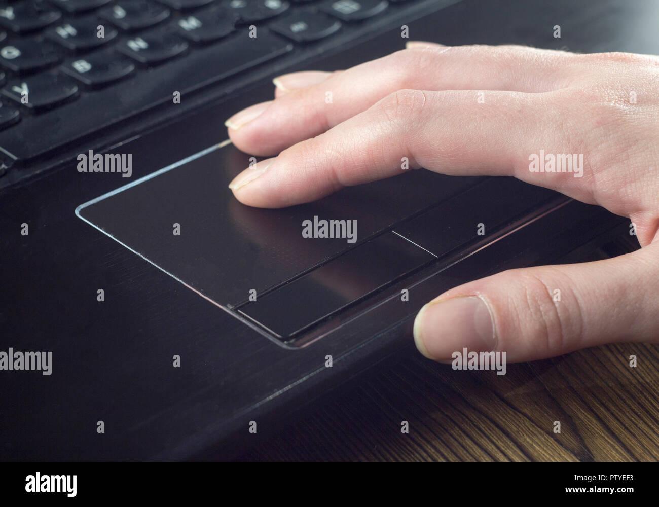 Main sur le pavé tactile de l'ordinateur portable Photo Stock