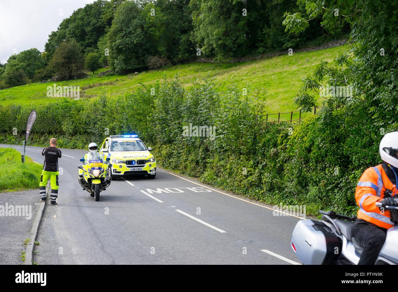 Voiture de police et sur la moto 2018 Cycle Tour de Grande-Bretagne comme il se dirige vers le village de Coniston, Cumbria, Angleterre, Royaume-Uni. Banque D'Images