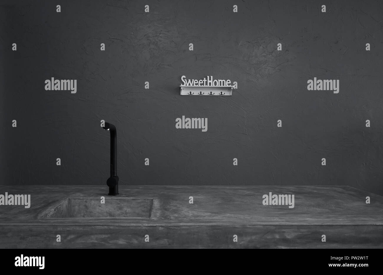 Noir moderne robinet et évier de la salle de cuisine avec comptoirs de ciment et d'herbe verte . Banque D'Images