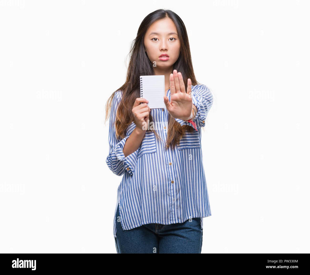 Young Asian woman holding notebook sur fond isolé avec main ouverte faisant stop avec de sérieux et de confiance, l'expression gestuelle de la défense Banque D'Images