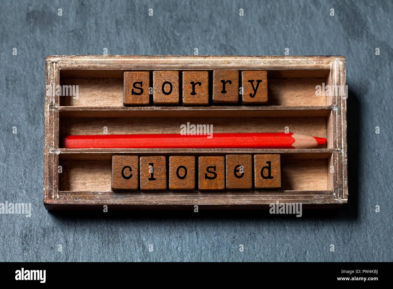 Désolés nous sommes fermés concept. Boîte en bois vintage, cubes de phrase par l'ancien style de lettres, crayon rouge. Fond texturé en pierre grise Photo Stock