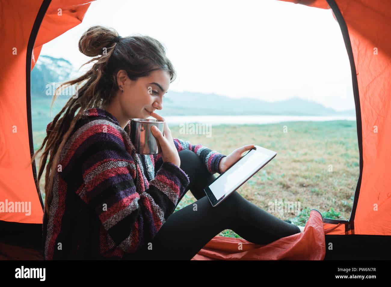 Close up un woman with digital tablet et boire une tasse de café un Photo Stock