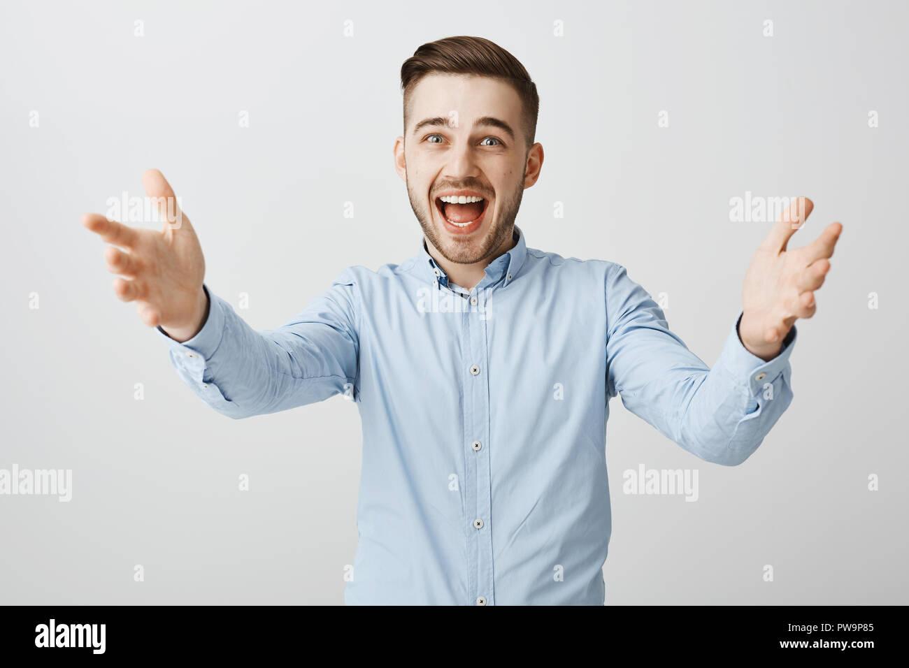 Taille plan sur heureux heureux beau beau mec avec adultes en soie bleu shirt officiel mains tirant vers la caméra avec un large sourire chaleureux invitant meilleur ami viennent dans Banque D'Images