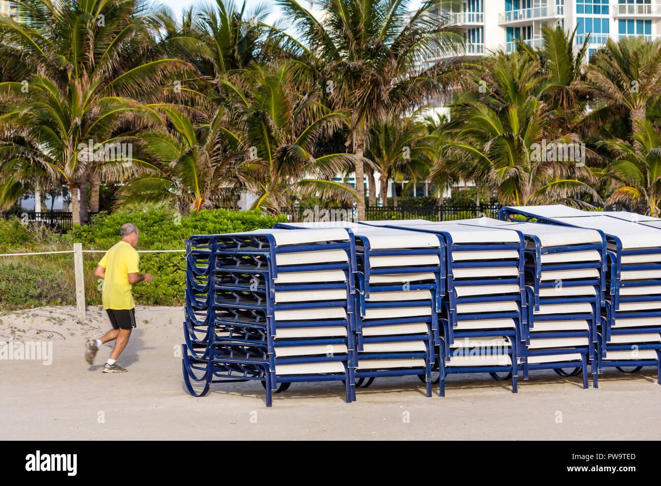 Miami Beach Florida plage publique de sable de South Beach lounge location de chaises empilées man jogging jogger palmiers remise en forme d'exercice il Photo Stock