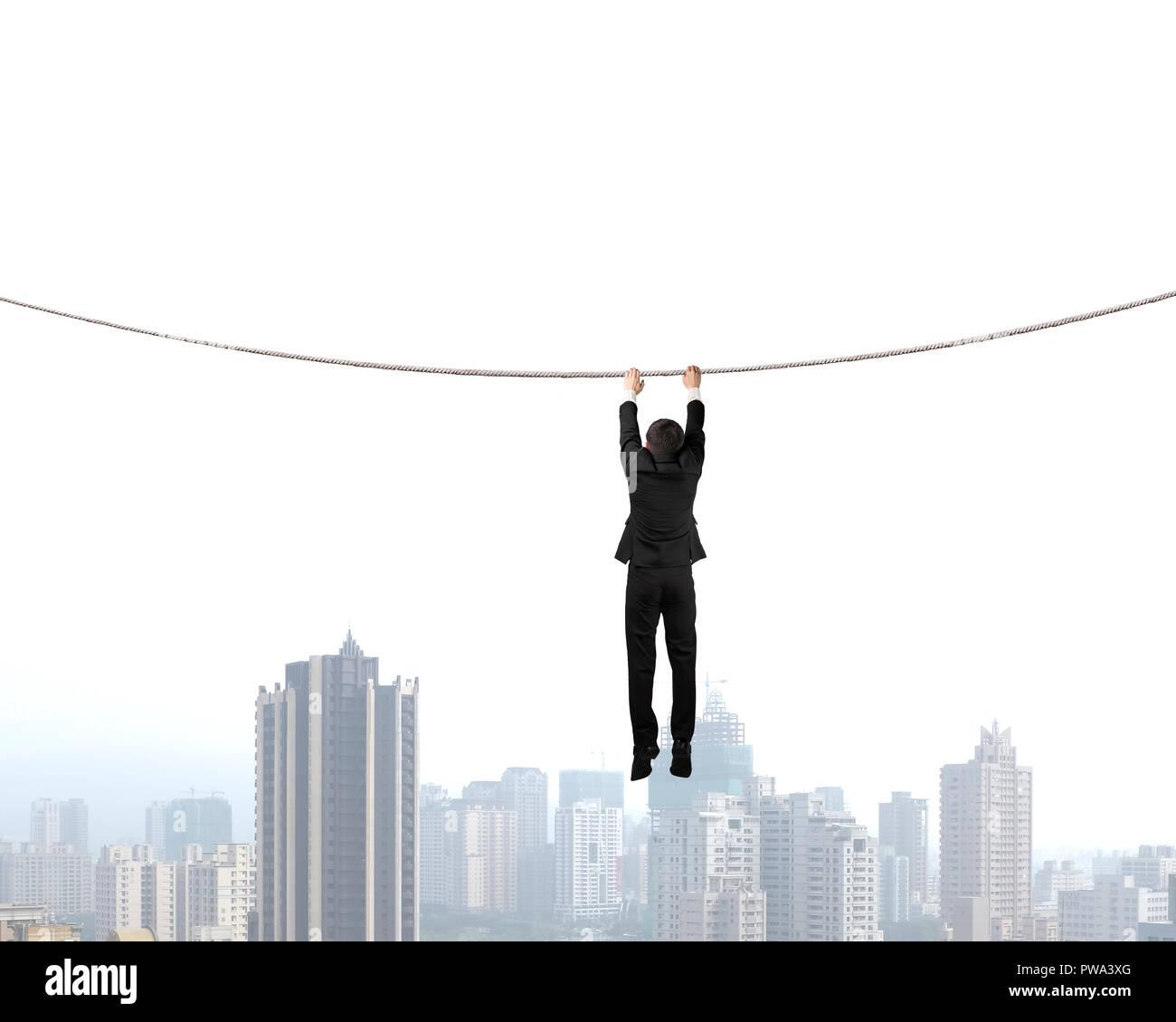Businessman holding rope et pendaison avec vue sur la ville Photo Stock