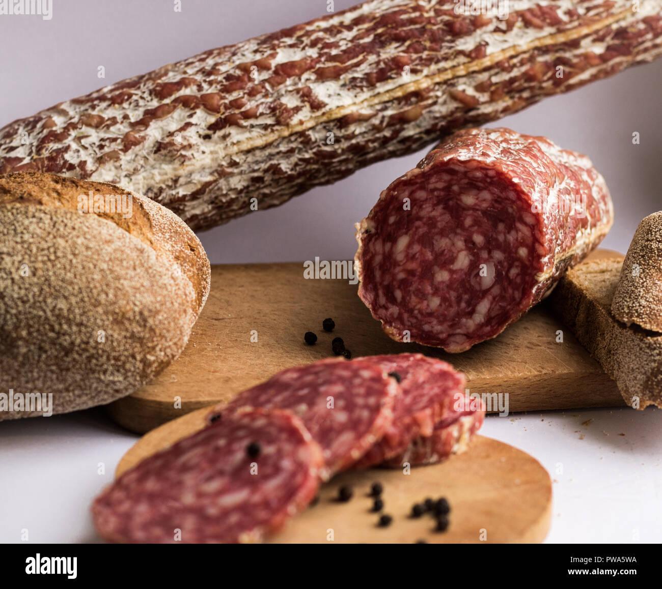 Des saucisses avec du pain et le poivre morceaux sur fond blanc Photo Stock