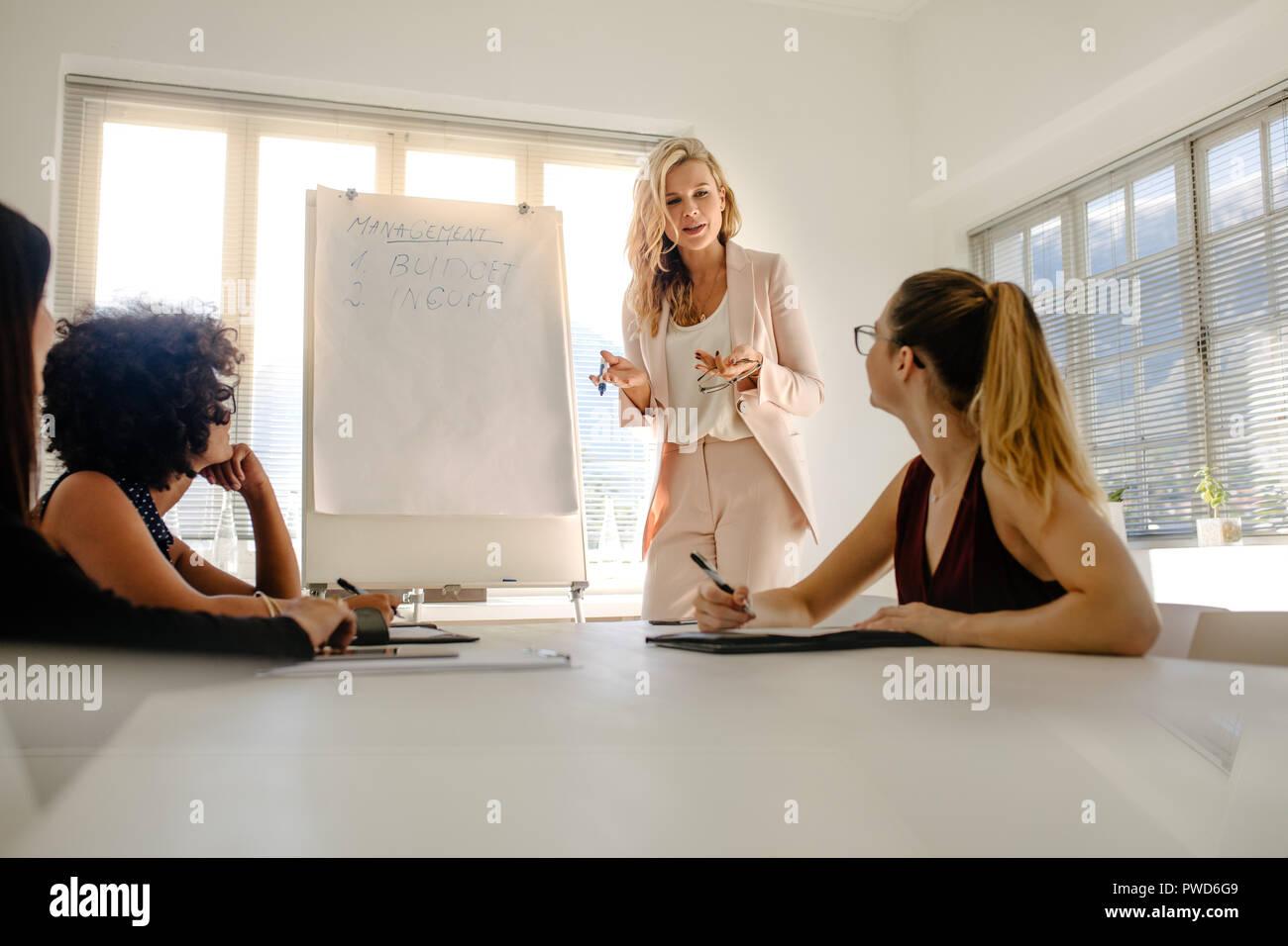 Femme manager discussing over budget et revenu avec vos collègues lors d'une réunion du conseil. Réunion du groupe des femmes d'avoir plus de financement. Photo Stock
