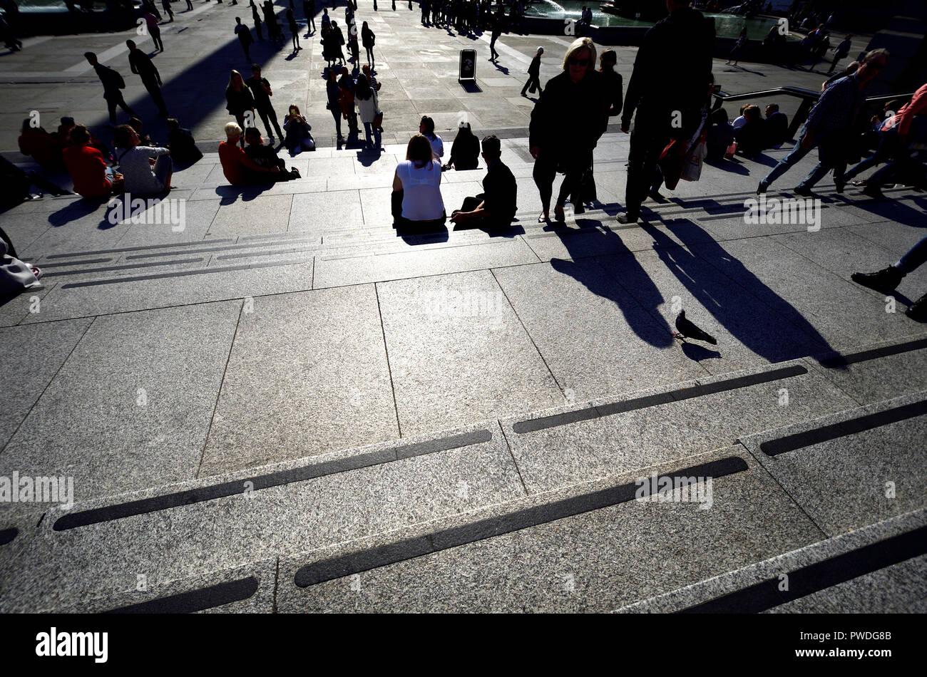 Les gens assis à Trafalgar Square, Londres, Angleterre, Royaume-Uni. Éclairé par led Banque D'Images
