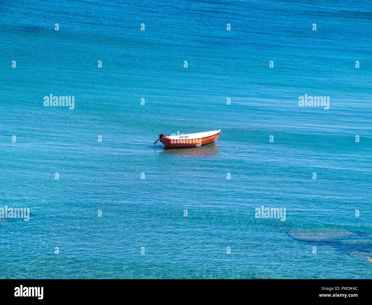 Petit bateau rouge, sans que personne à bord, au milieu de la mer bleue de la Calabre, de l'est côte italienne Photo Stock