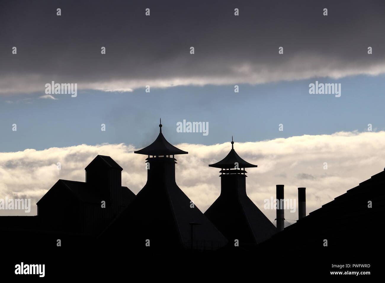 Les deux fours au Highland Park Distillery dans les Orcades, en Écosse, reconnaissables à leurs chapeaux en forme de pagode silhouetté contre le ciel bleu, les nuages. Banque D'Images