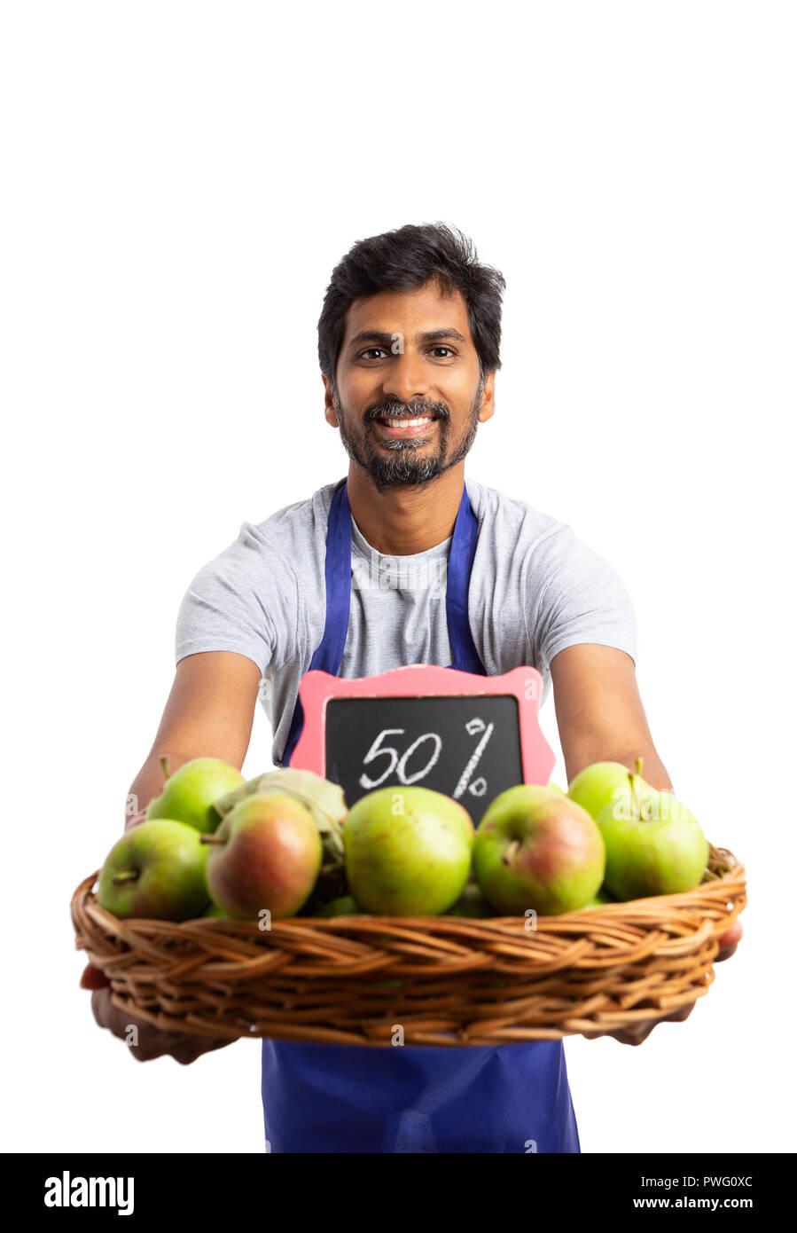 Supermarché indien smiling holding employé Apple organiques panier avec cinquante pour cent de réduction signe en tant que concept frais et sains isolated on white Photo Stock