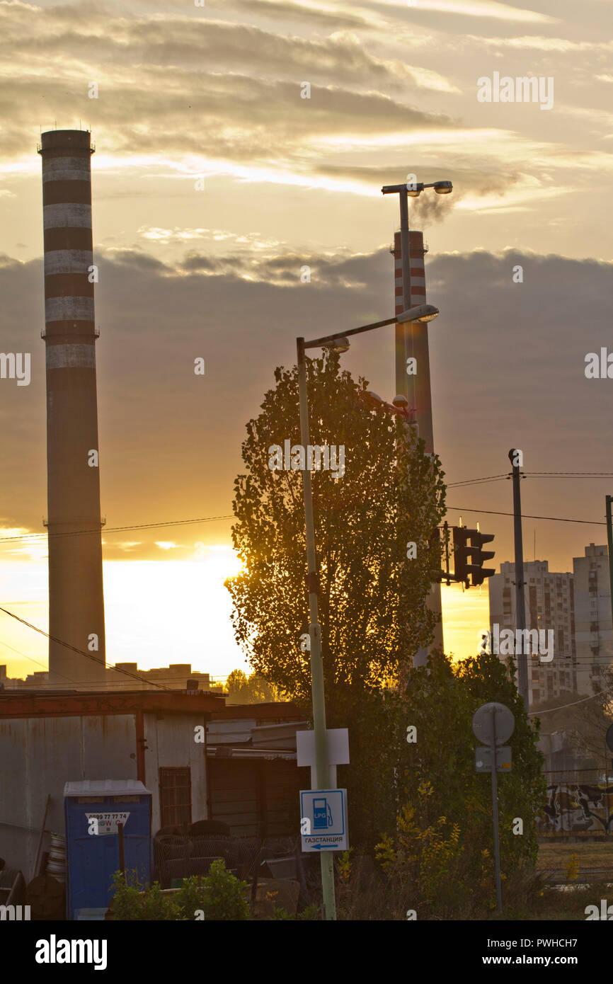 Centrale thermique du PPT sur un lever du soleil. Avec les cheminées de la raffinerie. La fumée d'usine pollue l'environnement. Rouge et blanc haute tour de CHPP. Ppt pr Photo Stock