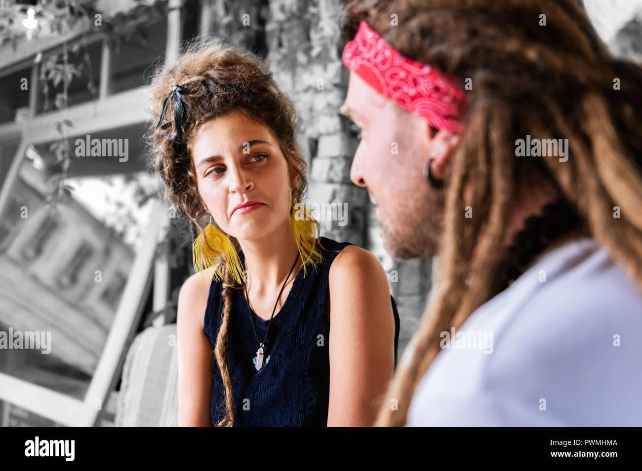 Femme cheveux bouclés avec chignon à à son amie tout en parlant de sa journée Photo Stock