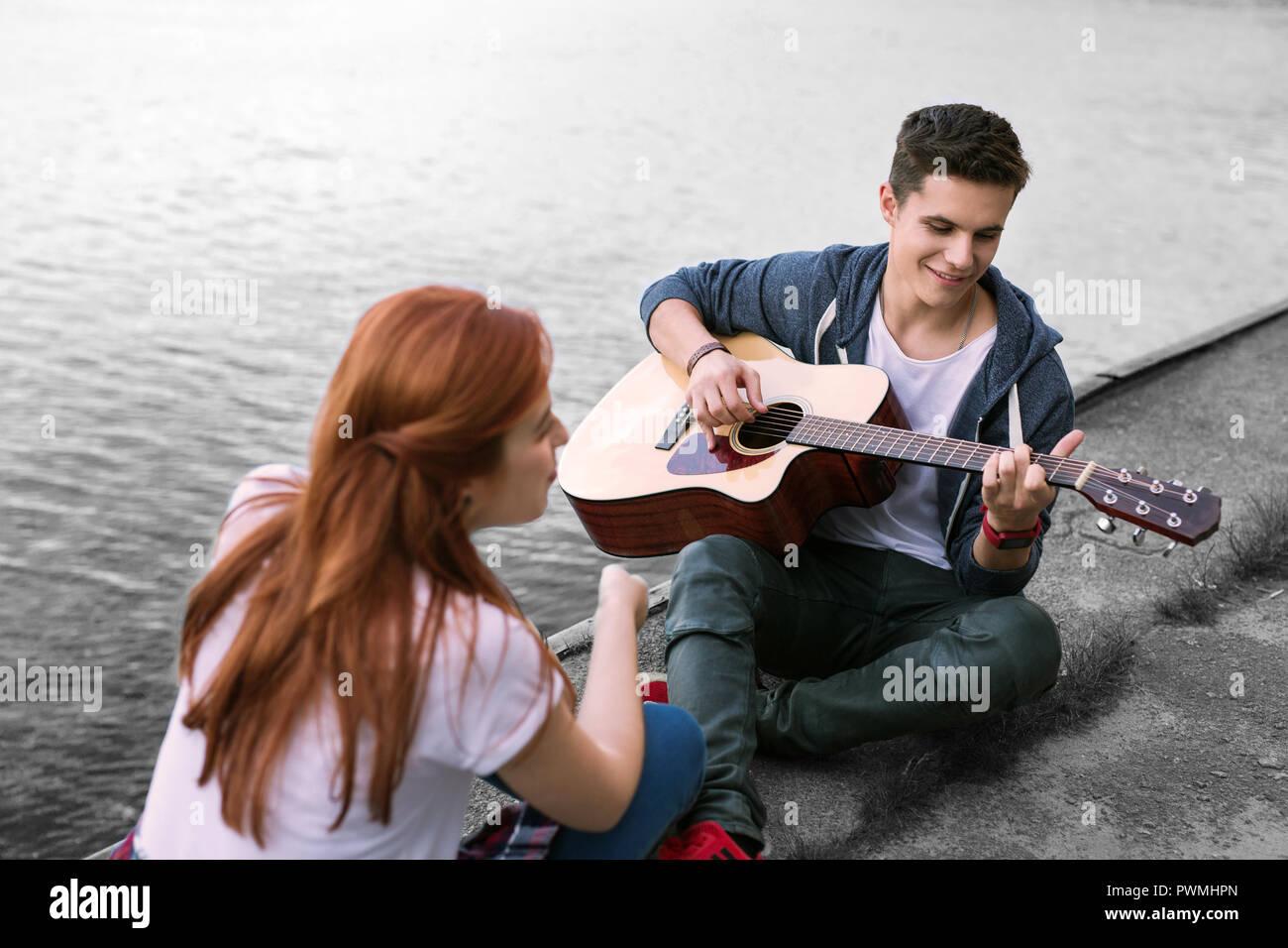 Beau petit ami romantique à jouer de la guitare pour sa petite amie assis près de river Photo Stock