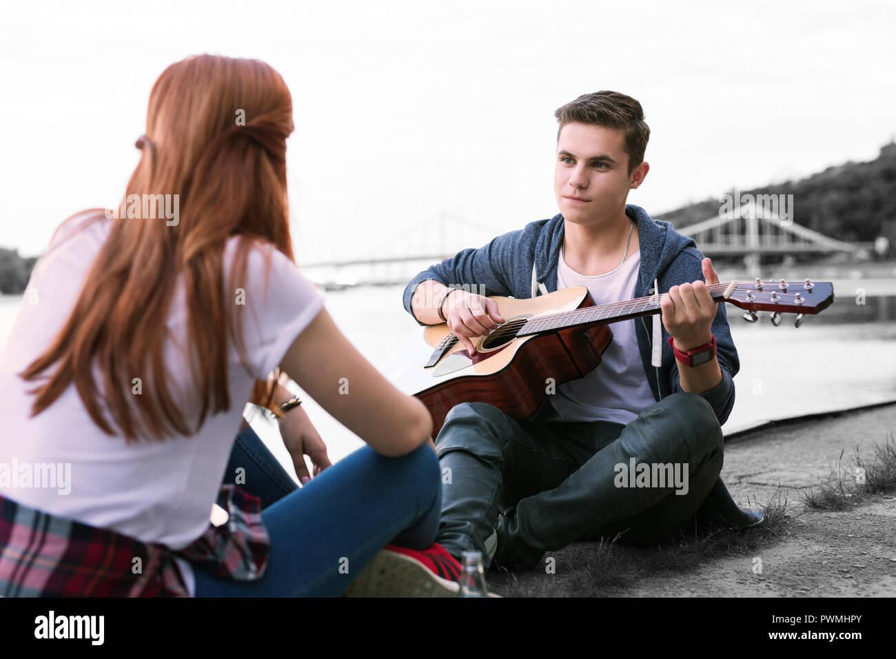 Beau garçon chanter la chanson pour sa petite amie assis près du pont Photo Stock