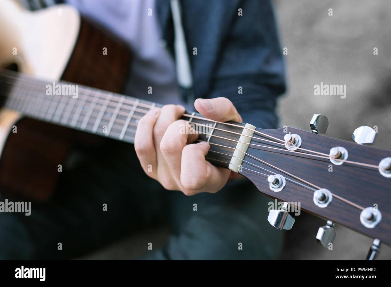 Close up of young boy portant des jeans et veste sport bleu à jouer de la guitare Photo Stock